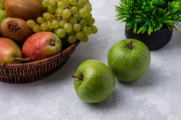 Vista frontal de manzanas verdes con uvas verdes pera y kiwi en una canasta sobre un fondo blanco.