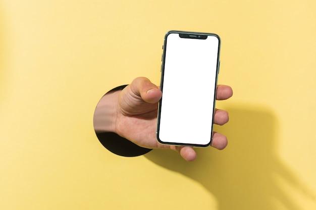 Vista frontal maqueta smartphone sostenido por persona