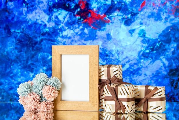 Vista frontal del marco de imagen en blanco presenta flores sobre fondo azul abstracto copia lugar