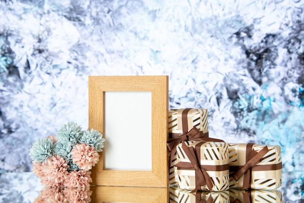 Vista frontal marco de imagen en blanco regalos de vacaciones sobre fondo abstracto claro
