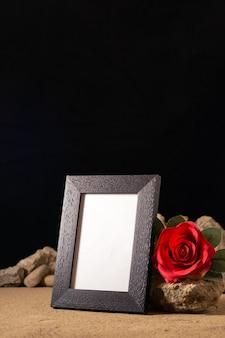 Vista frontal del marco de imagen vacío con flor roja y piedras sobre negro