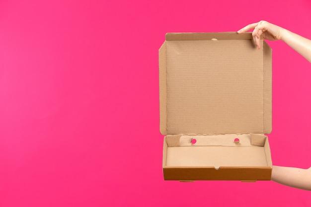 Una vista frontal marrón paquete vacío mano sujetando el paquete vacío mano femenina fondo rosa color alimentos