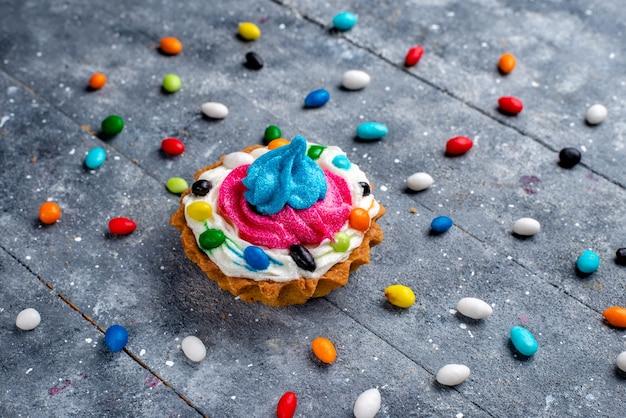 Vista frontal más cercana, pequeño y delicioso pastel con crema y diferentes caramelos de colores, todo a la luz