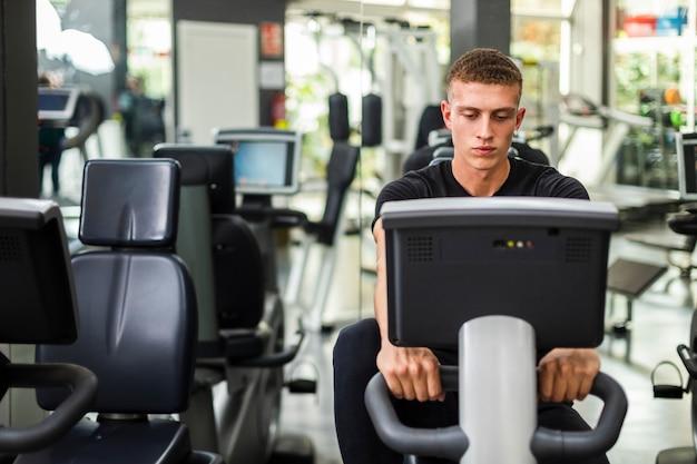 Vista frontal masculino en el gimnasio en bicicleta
