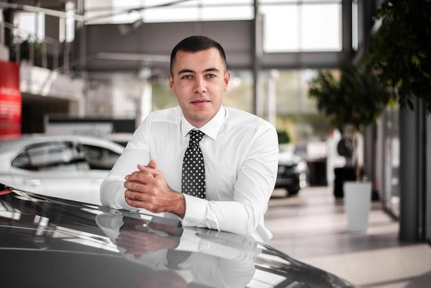 Vista frontal masculino parado en auto nuevo