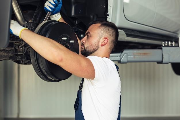Vista frontal mecánico masculino cambiando las ruedas del coche