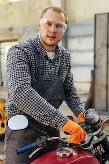 Vista frontal del mecánico masculino con gafas protectoras