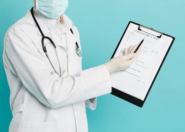 Vista frontal del médico apuntando a la prueba de coronavirus en su bloc de notas