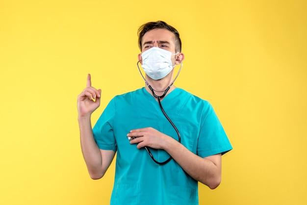 Vista frontal del médico con estetoscopio y máscara en la pared amarilla