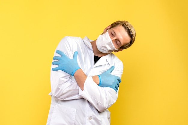 Vista frontal médico masculino abrazándose a sí mismo sobre fondo amarillo médico pandémico covid- salud
