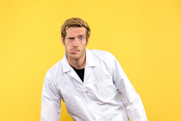 Vista frontal médico masculino con expresión divertida sobre fondo amarillo pandemia de médico covid humano