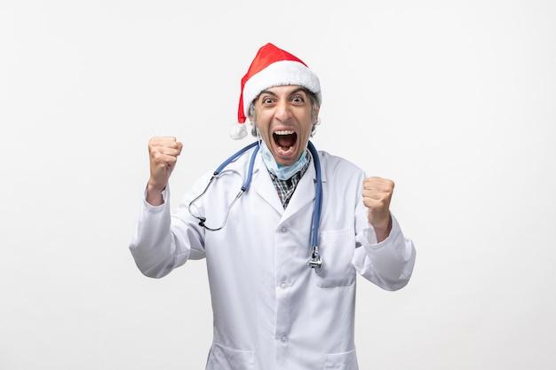 Vista frontal médico masculino gritando sobre la emoción de covid de vacaciones de virus de pared blanca