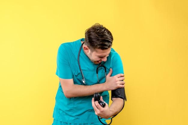 Vista frontal del médico masculino midiendo la presión en la pared amarilla