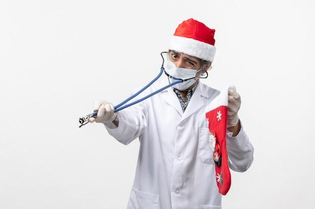 Vista frontal médico masculino observando el calcetín de vacaciones en la pared blanca virus covid holiday health