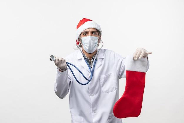 Vista frontal médico masculino observando el calcetín de vacaciones en la pared blanca virus covid salud en vacaciones