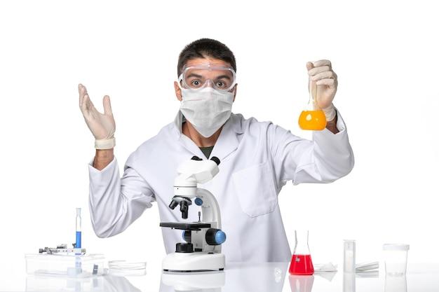 Vista frontal médico masculino en traje médico blanco con máscara debido a que covid trabaja con soluciones en el escritorio blanco