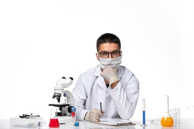 Vista frontal médico masculino en traje médico blanco y con máscara pensando en el espacio en blanco