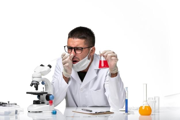 Vista frontal médico masculino en traje médico blanco y con máscara que trabaja con una solución en un espacio en blanco claro