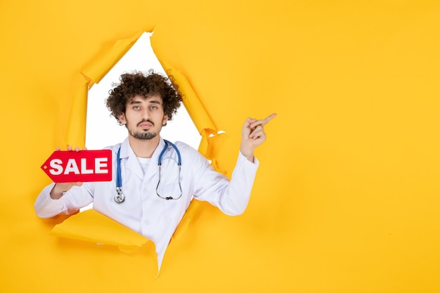 Vista frontal médico masculino en traje médico con venta roja escribiendo en amarillo médico color salud virus compras hospital