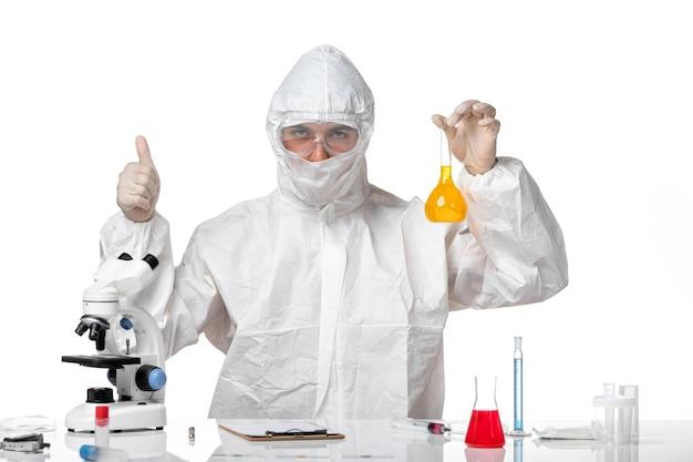 Vista frontal médico masculino en traje de protección con máscara debido al matraz de sujeción covid con solución amarilla en un espacio en blanco claro