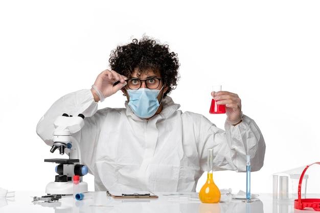 Vista frontal médico masculino en traje de protección y máscara con matraz con solución roja sobre fondo blanco virus de la epidemia del covid pandémico