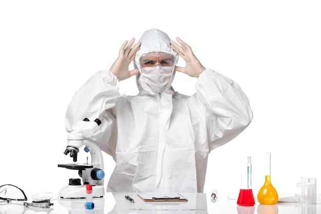 Vista frontal médico masculino en traje protector con máscara debido a covid sentado en un espacio en blanco