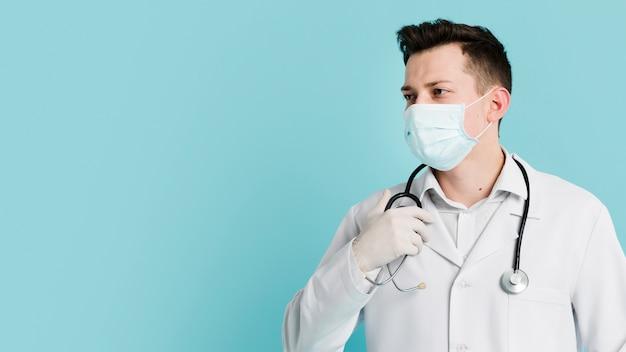 Vista frontal del médico posando con estetoscopio y máscara médica