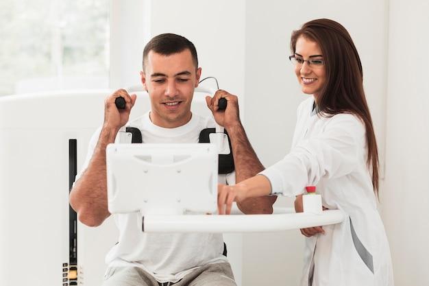 Vista frontal médico que muestra al paciente cómo usar la máquina médica