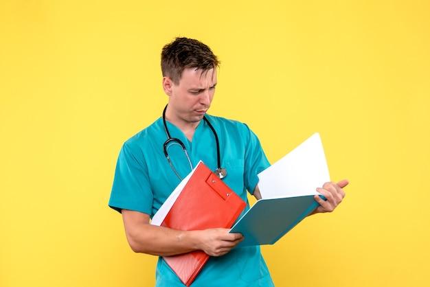 Vista frontal del médico de sexo masculino que controla los análisis en la pared amarilla