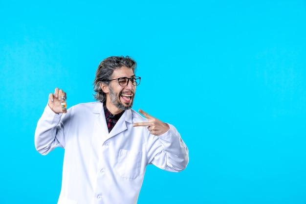 Vista frontal médico de sexo masculino en uniforme médico sosteniendo pequeño frasco en el azul