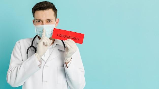 Vista frontal del médico sosteniendo papel con coronavirus y haciendo la señal silenciosa
