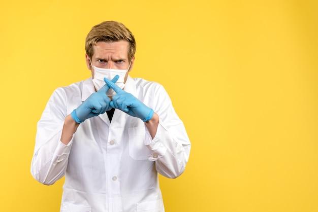 Vista frontal médico varón cruzando los dedos sobre fondo amarillo pandemia covid- virus de salud