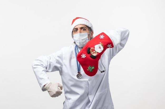 Vista frontal médico varón con gran calcetín rojo sobre piso blanco virus covid- vacaciones de navidad