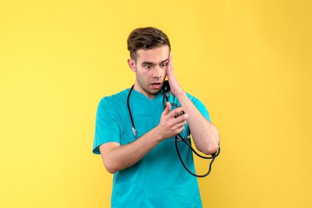 Vista frontal del médico varón midiendo su presión sobre la pared amarilla