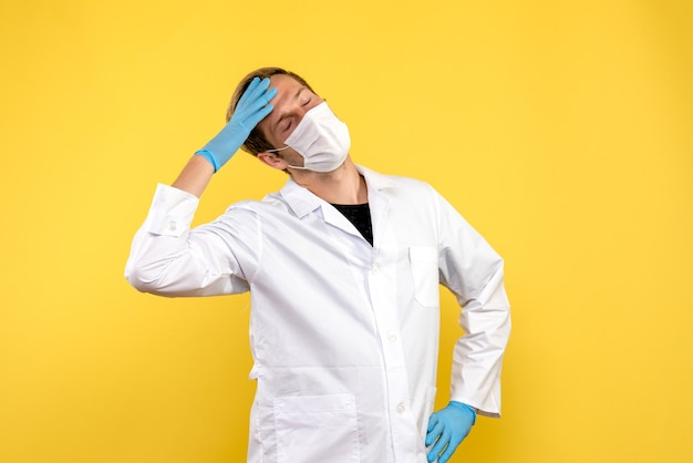 Vista frontal médico varón que tiene dolor de cabeza sobre fondo amarillo pandemia de virus covid de salud