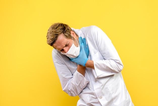 Vista frontal médico varón que tiene problemas respiratorios sobre fondo amarillo médico pandémico covid-