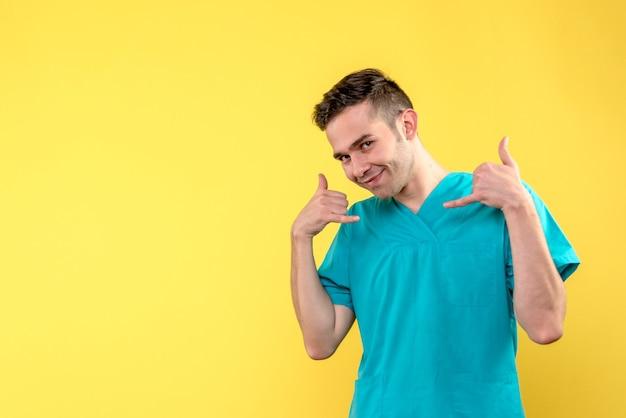 Vista frontal del médico varón sonriendo sobre pared amarilla