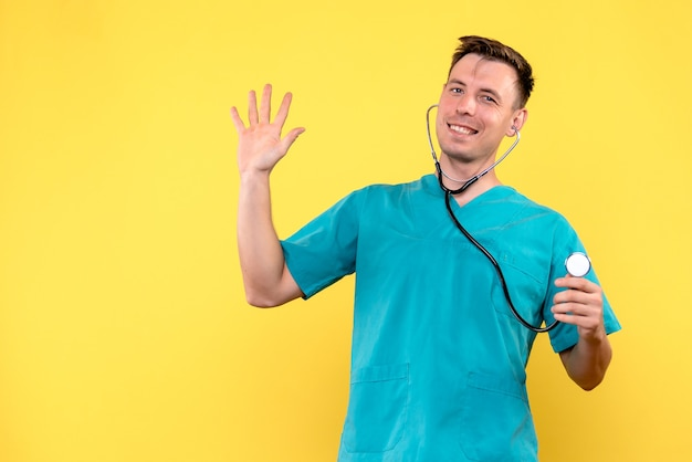 Vista frontal del médico varón sonriendo con tonómetro en pared amarilla