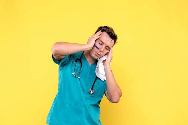 Vista frontal del médico varón sosteniendo documentos en la pared amarilla