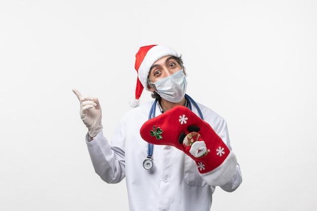 Vista frontal médico varón sosteniendo un gran calcetín rojo en la pared blanca virus covid- vacaciones