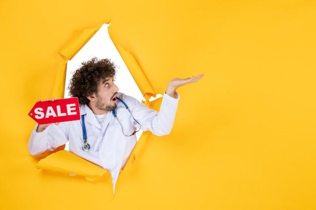 Vista frontal médico varón en traje médico sosteniendo venta escrito en color amarillo compras médico de hospital de medicina de salud