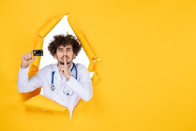 Vista frontal médico varón en traje médico con tarjeta bancaria en el color amarillo medicina hospital enfermedad salud virus medic