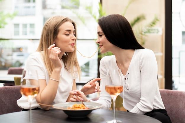 Vista frontal mejores amigos comiendo el mismo fideos spaghetti
