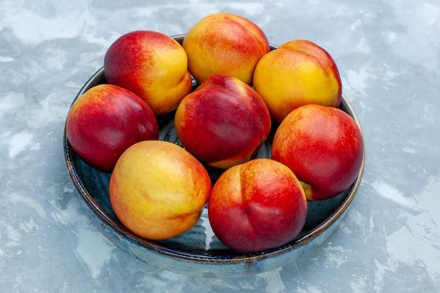 Vista frontal melocotones frescos deliciosas frutas de verano en escritorio blanco claro