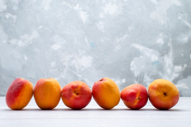 Una vista frontal melocotones frescos y suaves sobre el fondo blanco color de la fruta verano jugoso fresco