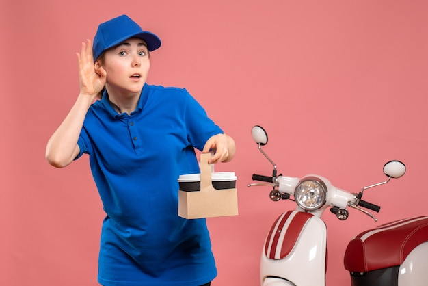 Vista frontal de mensajería femenina con café de entrega en bicicleta rosa trabajo servicio de entrega trabajadora mujer uniforme trabajo