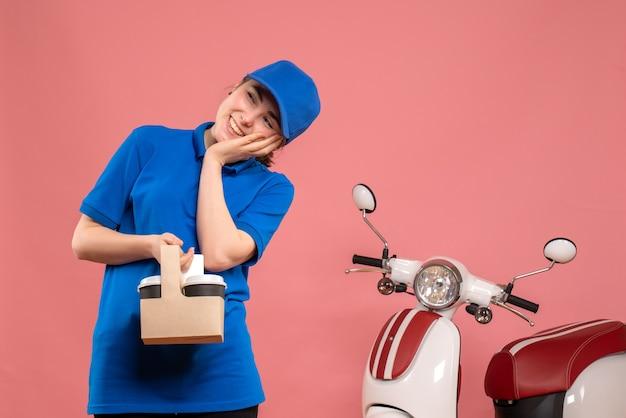 Vista frontal de mensajería femenina con café de entrega en el escritorio rosa, servicio de entrega de trabajo, trabajador, mujer, bicicleta, uniforme, trabajo