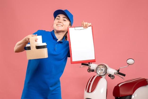 Vista frontal de mensajería femenina con café y nota de archivo sobre el servicio de uniforme de entrega de trabajo rosa trabajador de trabajo pizza mujer bicicleta