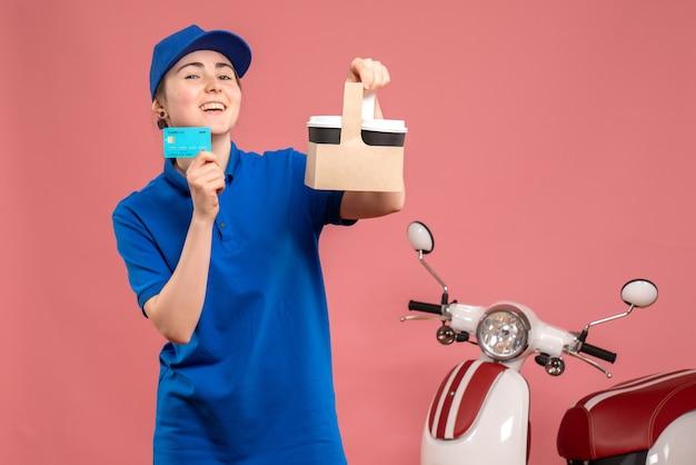 Vista frontal de mensajería femenina con café y tarjeta bancaria en rosa trabajo servicio uniforme de entrega de trabajo trabajador pizza mujer bicicleta