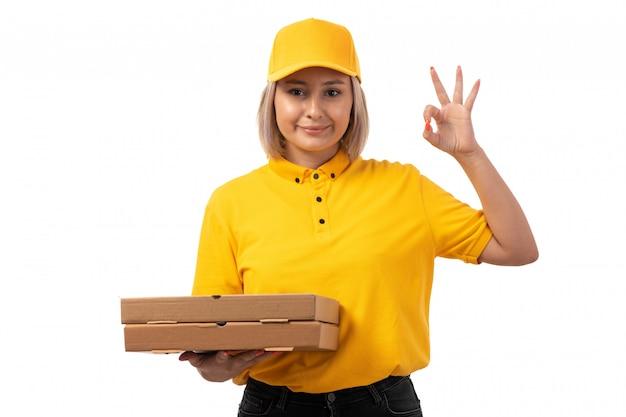 Una vista frontal de mensajería femenina en camisa amarilla gorra amarilla jeans negros con cajas de pizza sonriendo en blanco